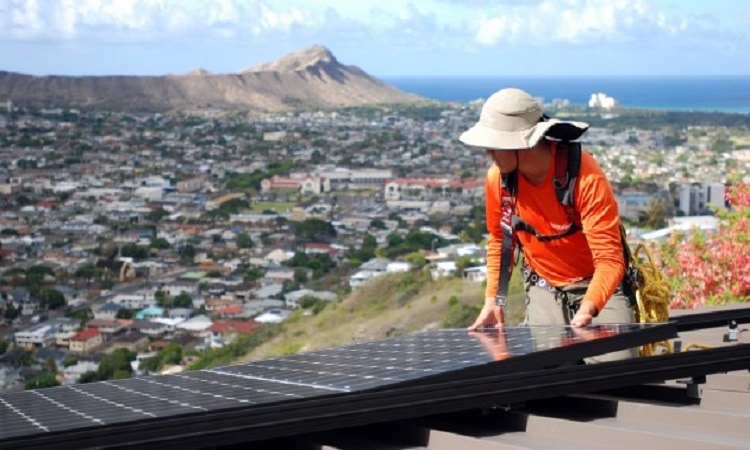 Man in hat leaning over solar panel (© AP Images)