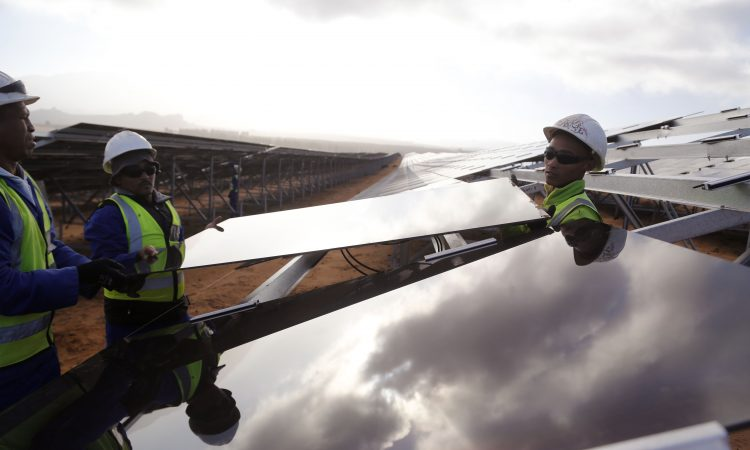 Three men holding solar panel (© AP Images)