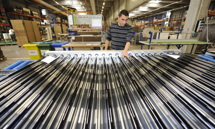 Man standing in warehouse with array of silver rods (© AP Images)