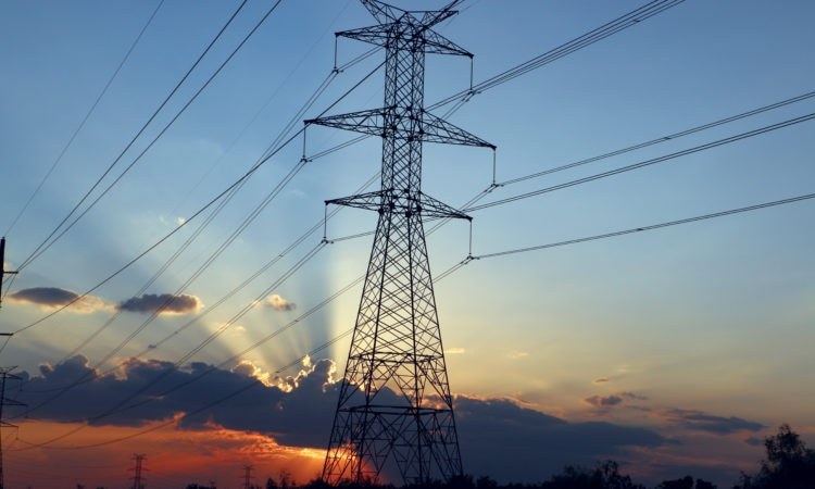 Power transmission lines and towers, clouds and sunset behind (ERCOT)