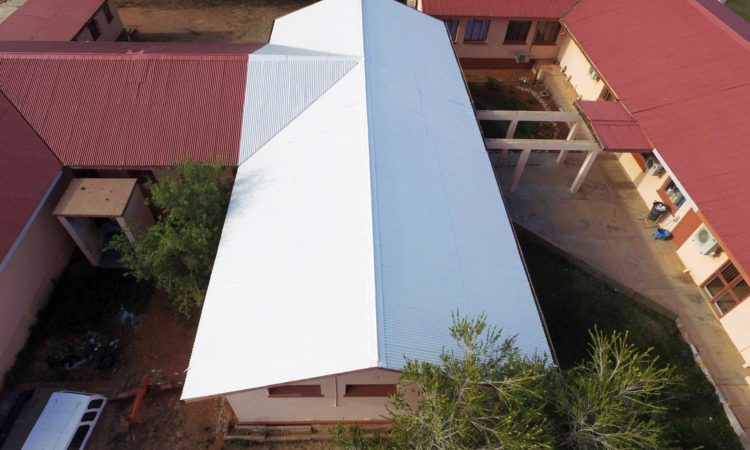 Long white pitched roof and adjacent red roofs (PEER Africa)