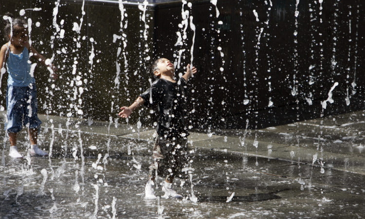 Water from fountain falling on playing children (© AP Images)