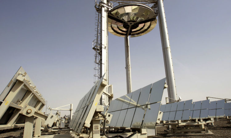 Tall mirrored tower above solar panel arrays (© AP Images)